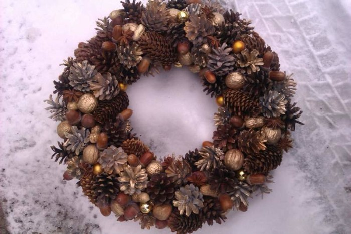 many fir cones and pinecones, acorns and wallnuts, some decorated with gold spray paint, stuck together to form a wreath, holiday wreaths, placed on a snowy surface