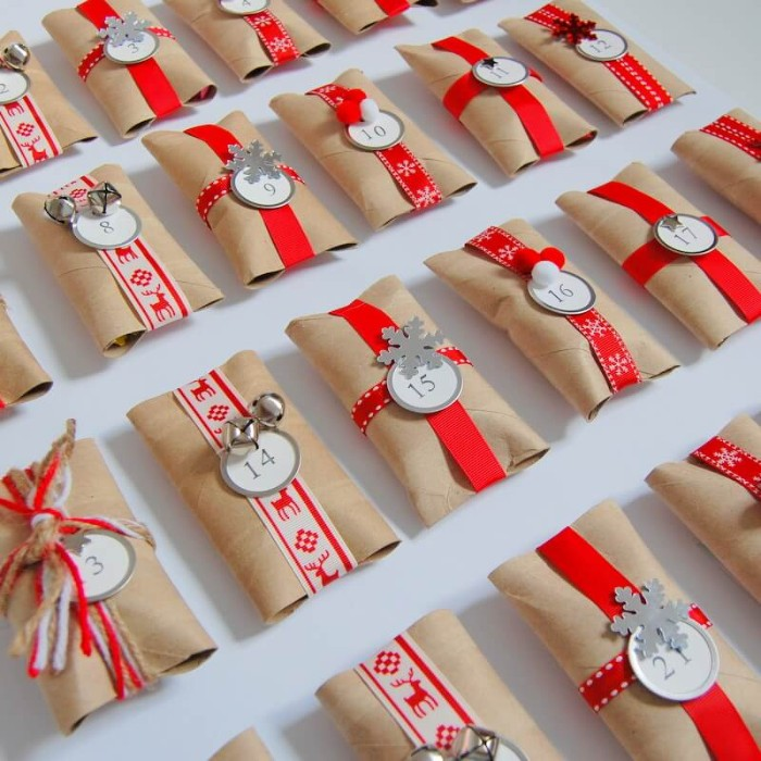 gift wraps made from toilet paper rolls, decorated with red and white patterned ribbon, yarn and plain red ribbon, with small round, numbered labels and bells, snowflake shapes and other decorations, advent calendar ideas, seen in close up
