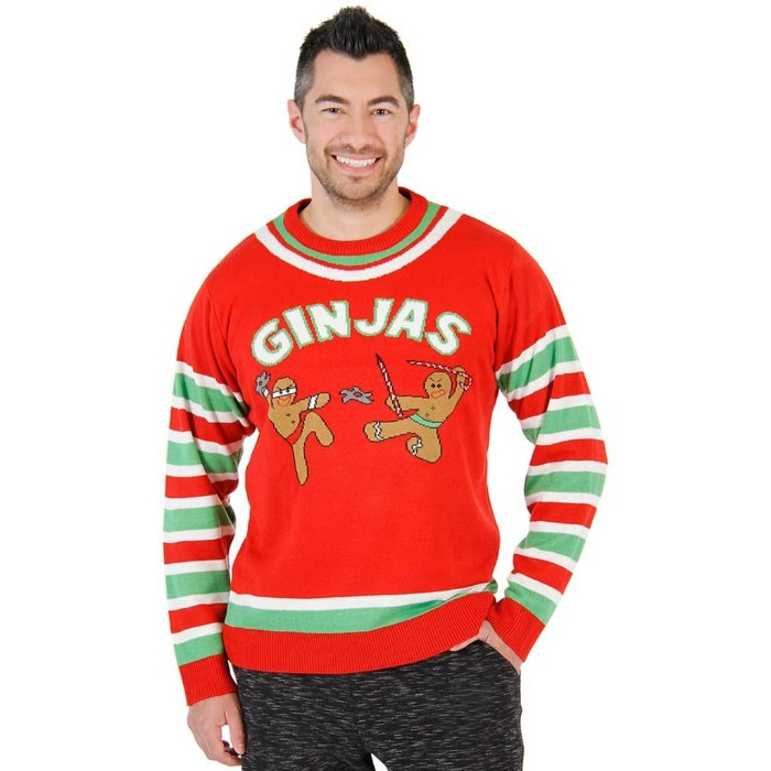 gingerbread men dressed like ninjas, on an orange-red cute ugly christmas sweater, with white and light green stripes, and the word ginjas, worn by a smiling man