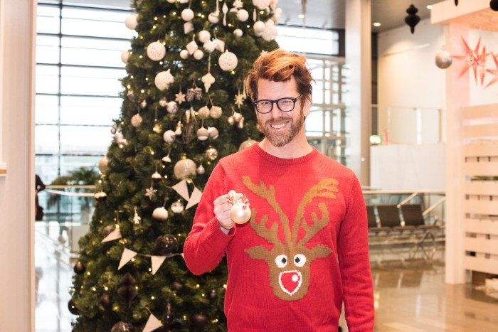 bespectacled man with a short beard, wearing a red sweater, featuring an image of a brown cartoon deer's head, with a red nose