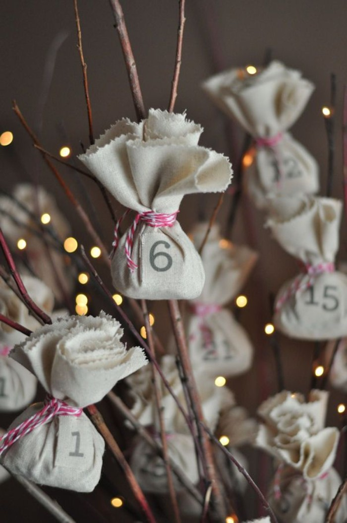 little numbered bundles, made from light cream fabric, tied with a striped, red and white string, attached to dry brown branches, decorated with small, glowing fairy lights