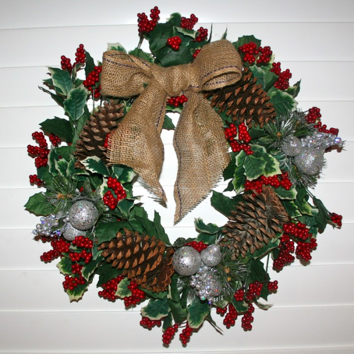 fir cones and small red berries, on a diy christmas wreath, made from green leaves, and decorated with small silver baubles, and a large burlap bow