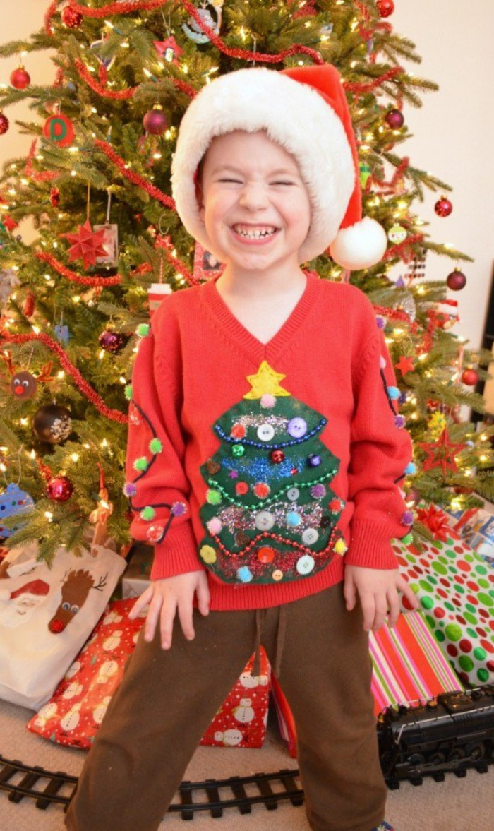 boy wearing a red v-neck jumper, decorated with a christmas tree motif, made from green and yellow felt, and decorated with beads in different colors, diy ugly christmas sweater for kids