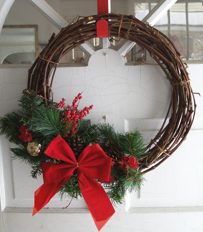 thin brown branches, twisted together to form a christmas wreath, decorated with fir leaves, small red berries, little pine cones, a big red bow, and red and gold baubles