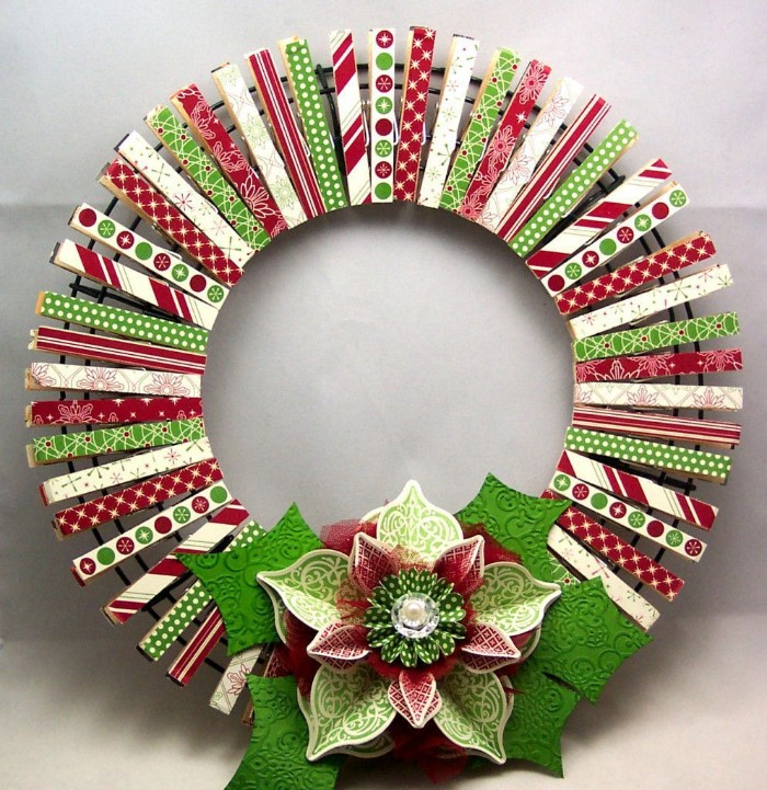 pegs made of wood, decorated with paper decoupage, featuring green and red, and white patterns, clipped onto a round metal frame, to form a wreath, decorated with a large paper flower, wreath ideas
