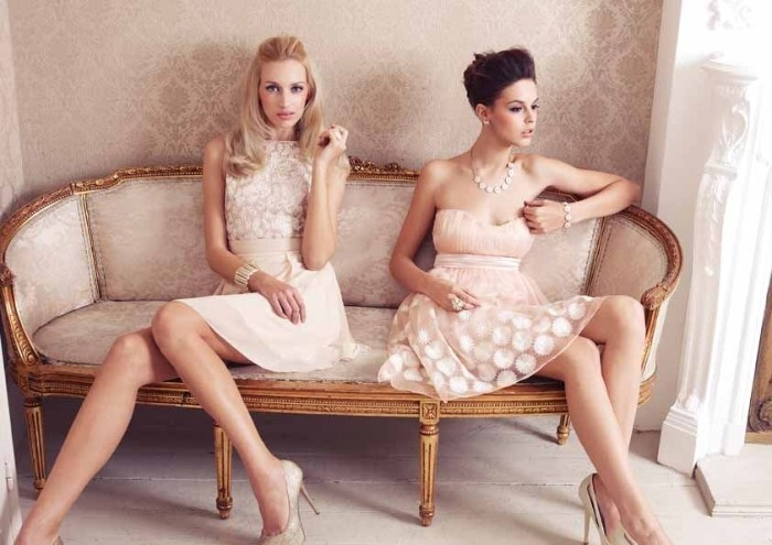 light peach occasion mini dresses, with white lace details, cocktail attire for women, worn by two slim models, sitting on an antique pale beige couch