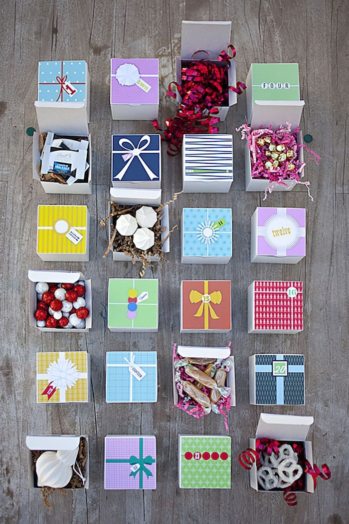 square boxes in different colors, placed on a grayish wooden surface, some of the boxes are opened, revealing treats and christmas ornaments
