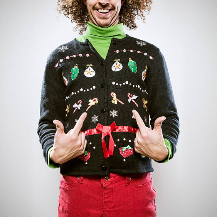 ugliest christmas sweater, man with medium length, brown curly hair, wearing a light green turtleneck, coral red trousers, and a black cardigan, with colorful festive motifs, and a shiny red ribbon