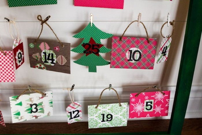 countdown to christmas calendar, made with numbered, colorful patterned pieces of card, some featuring cord handles, attached with miniature pegs, to of wire or string