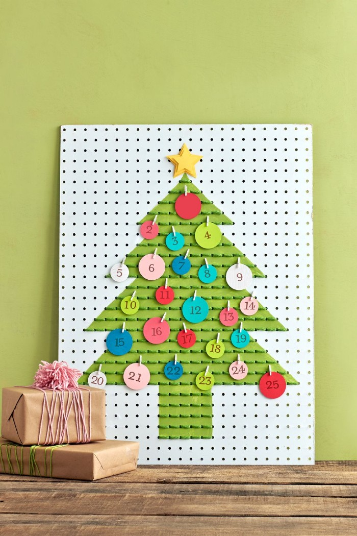 board with multiple holes, featuring a christmas tree shape, painted in green, and decorated with green thread, christmas countdown calendar, round small labels, in different colors and sizes, attached with miniature pegs