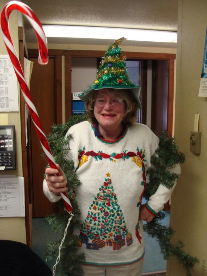 hat in green, shaped like a christmas tree, and decorated with garlands and baubles, worn by an elderly woman, dressed in a white jumper, featuring an xmas tree, and holding a giant peppermint cane