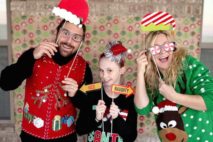 family with a mom, dad and a daughter, all dressed in different tacky festive jumpers, ugliest christmas sweater, red with an xmas tree, black with a festive message, green with white polka dots, and a cartoon deer's head