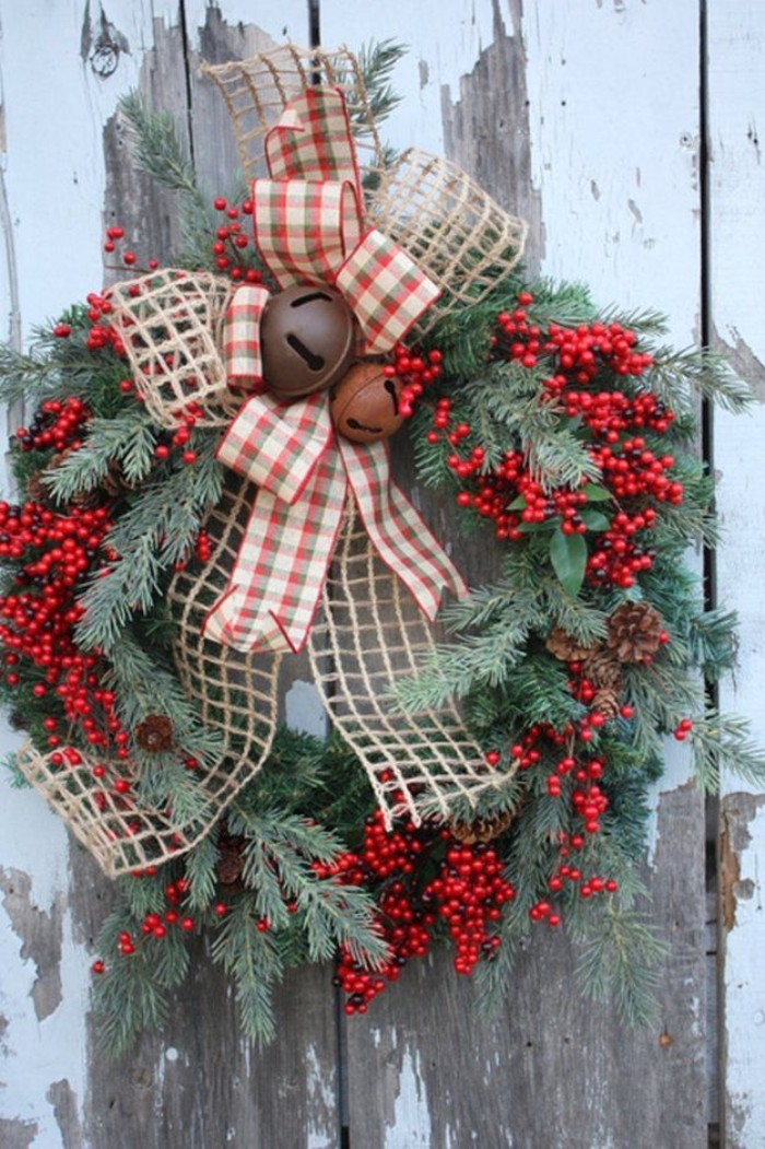 bells in rusty orange and borwn, decorating a wreath, made from pine branches, adorned with multiple red berries, and large bows, made of burlap, and a checkered fabric