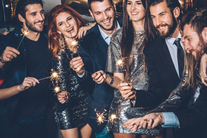 lit sparkles held by a group of smiling people, men wearing dark suits, some with pale shirts and black ties, women in sparkling silver sequin dresses, black tie optional outfit ideas