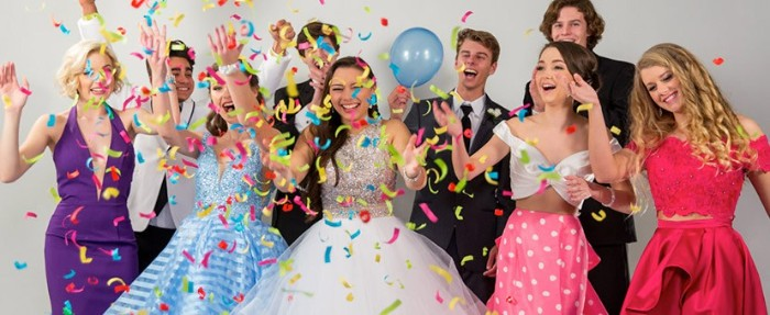 multicolored confetti and a blue balloon, next to a group of celebrating teenagers, wearing prom dresses, and formal suits