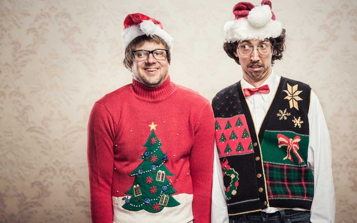two men wearing festive, multicolored sweater and vest, and stanta hats in red and white, ugly christmas sweater ideas, xmas trees and bows, snowflakes and a wreath