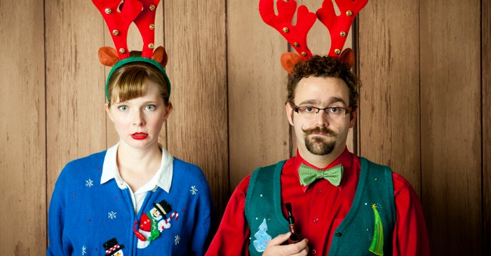 couple with red and green headbands, featuring deer ears and antlers, the woman is wearing a blue cardigan with snowmen, and the man is dressed in a red shirt, forest green vest, and light green bowtie, ugly christmas sweater ideas for grownups