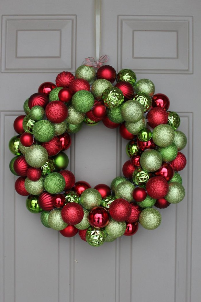 sparkling baubles in red, and two shades of green, stuck together to form a diy christmas wreath, hanging on a white door