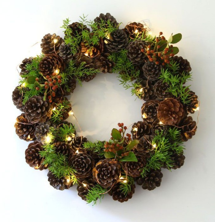 glowing string lights, decorating a christmas wreath, made from pinecones, and little green leaves, with small berries, on a white surface