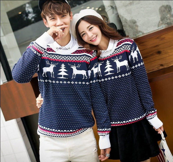 identical navy blue sweaters, with white and red fair isle motifs, featuring deer and christmas trees, worn by a young smiling couple, ugly sweater party