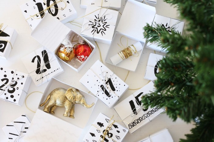 white boxes with numbers, written on them in black, some open and some closed, the open ones contain a metallic, gold elephant figurine, christmas tree ornaments, and other items, advent calendar ideas, fake christmas tree branches nearby