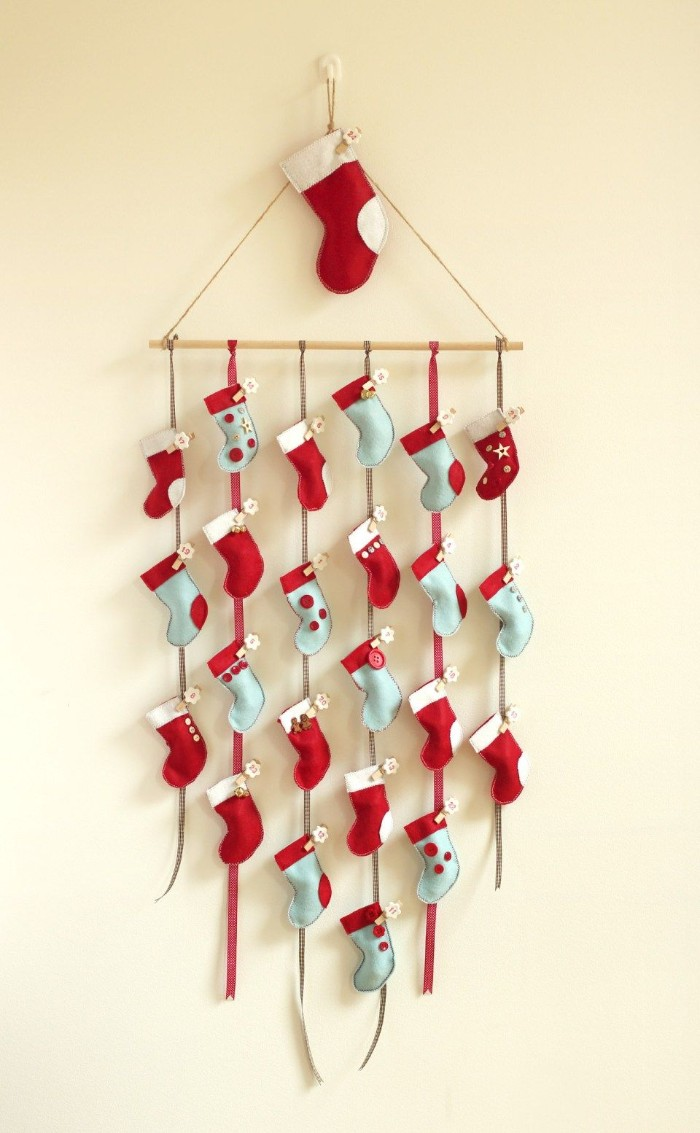 light blue and red, miniature stockings with white details, made from felt, attached to six pieces of string, tied to a small wooden pole, creative christmas countdown calendar, you can make yourself