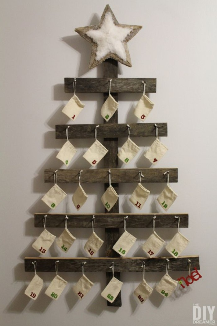 pieces of wood, attached together to form a minimalistic christmas tree, with a star on top, the three is decorated with 24 small, numbered pale cream drawstring bags, hanging on nails