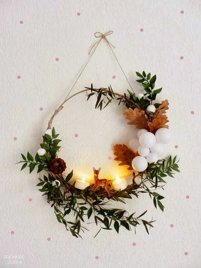autumnal oak leaves, in light brown, a small deer figurine, and two lit tea lights, decorating a wreath, made from thin branches, featuring small green leaves, christmas wreath ideas
