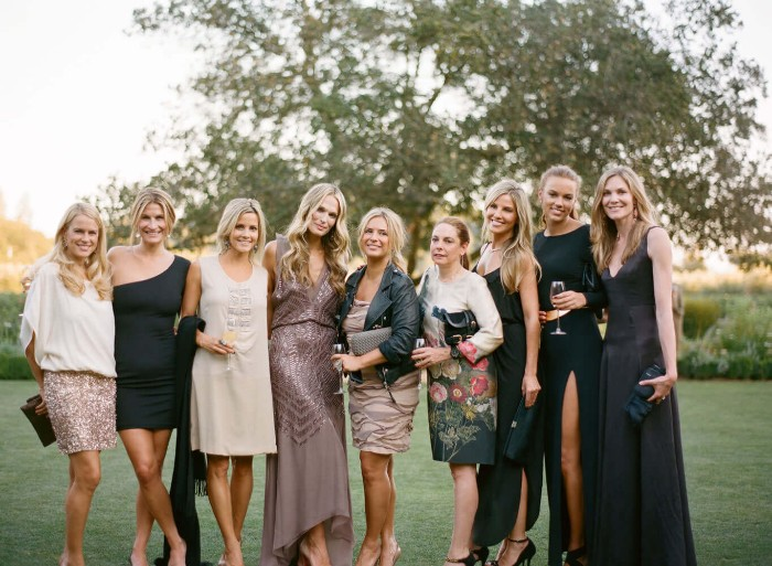 group photo of nine smiling blonde women, dressed in cocktail attire, maxi and midi dresses in black, white and ash pink, and featuring floral patterns