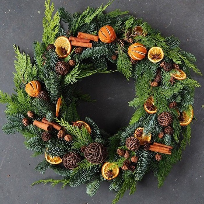 dried orange slices and peel, and cinnamon sticks, decorating a christmas wreath, made from fir, and pine branches and leaves