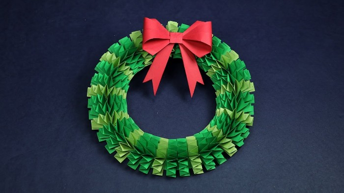 paper christmas wreath, in two shades of green, folded origami style, and decorated with a red, paper bow on top
