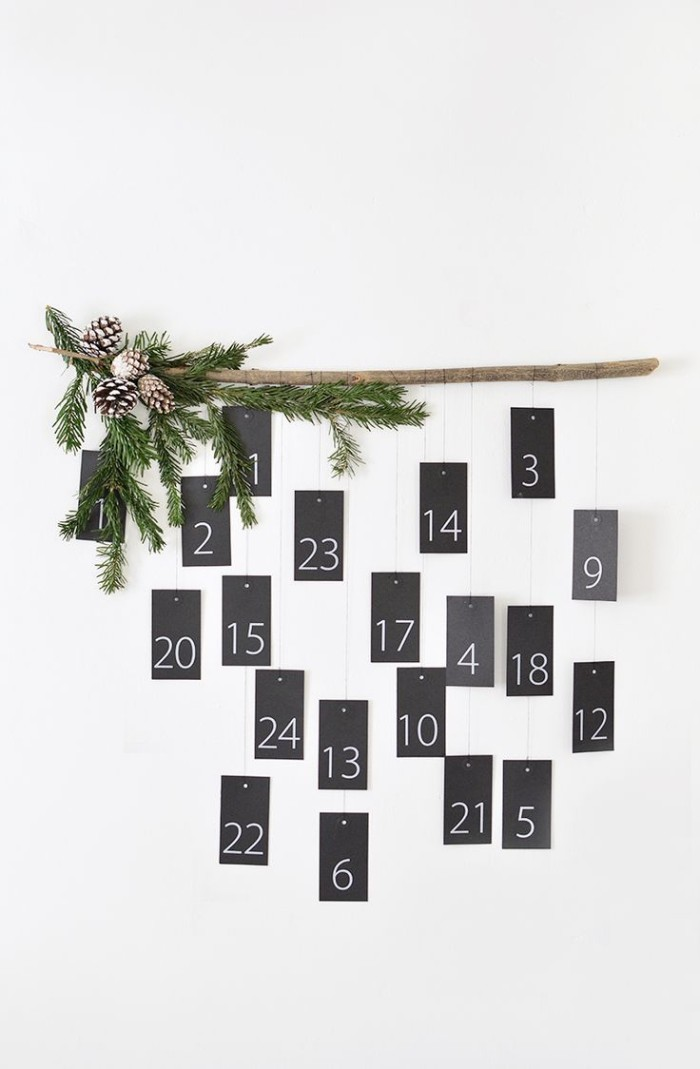 black cards hanging on pieces of string, from a wooden pole, decorated with pine cones, and fir branches, each card has a white number, from 1 to 24, christmas countdown calendar
