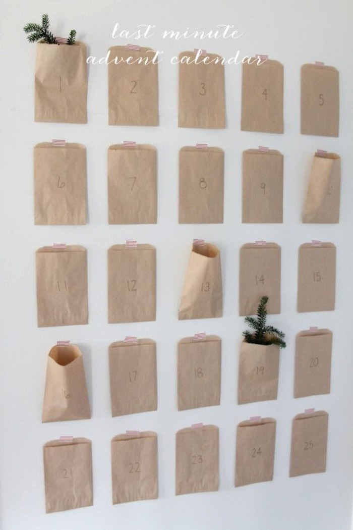 minimalistic advent calendar, made of 25 small, numbered beige paper bags, stuck to a white wall, each bag features a number, from 1 to 25