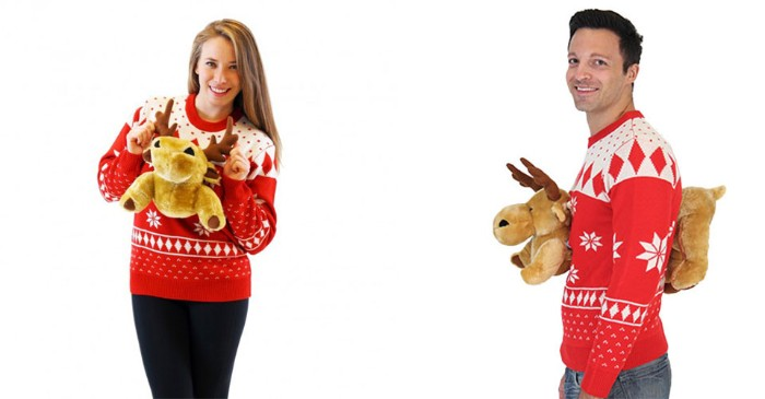 plush reindeer toys, stuck to the front, and the back, of two white and red jumpers, worn by a brunette woman, and a dark-haired man