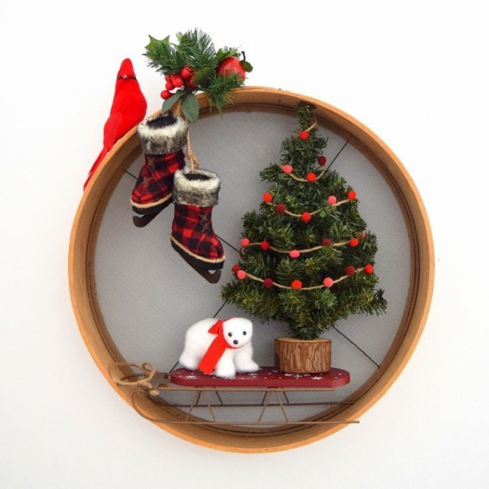 christmas wreath, made from a wooden hoop, decorated with a christmas tree figurine, a small polar bear toy, with a red scarf, a sleigh and a pair of ice skates, a little red bird, a prig of holly and pine leaves