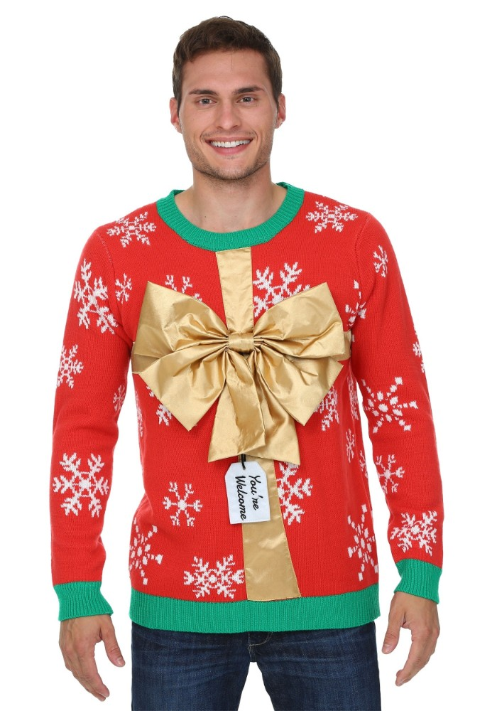 shiny gold large bow, on a red jumper, with white snowflake pattern, and green trims on its cuffs, collar and hem, ugly christmas sweater ideas, on a smiling young man