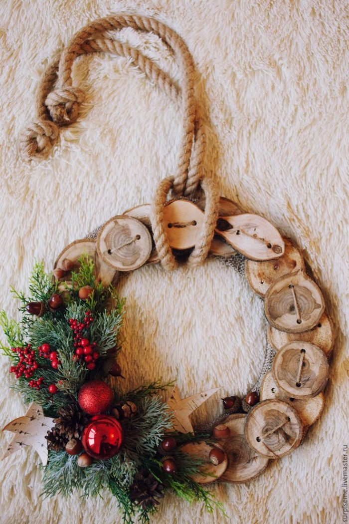 rope tied around a wreath, made from round wooden shapes, perforated and tied together, holiday wreaths, decorated with pine leaves, small red berries, red baubles and a star shape, made from white birch bark