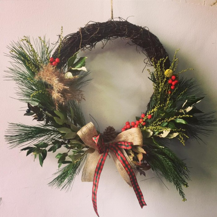 pine leaves and sprigs from other green, and dried plants, decorating a rustic-style wreath, made from thin, dried and twisted branches, and adorned with bows, and a pinecone