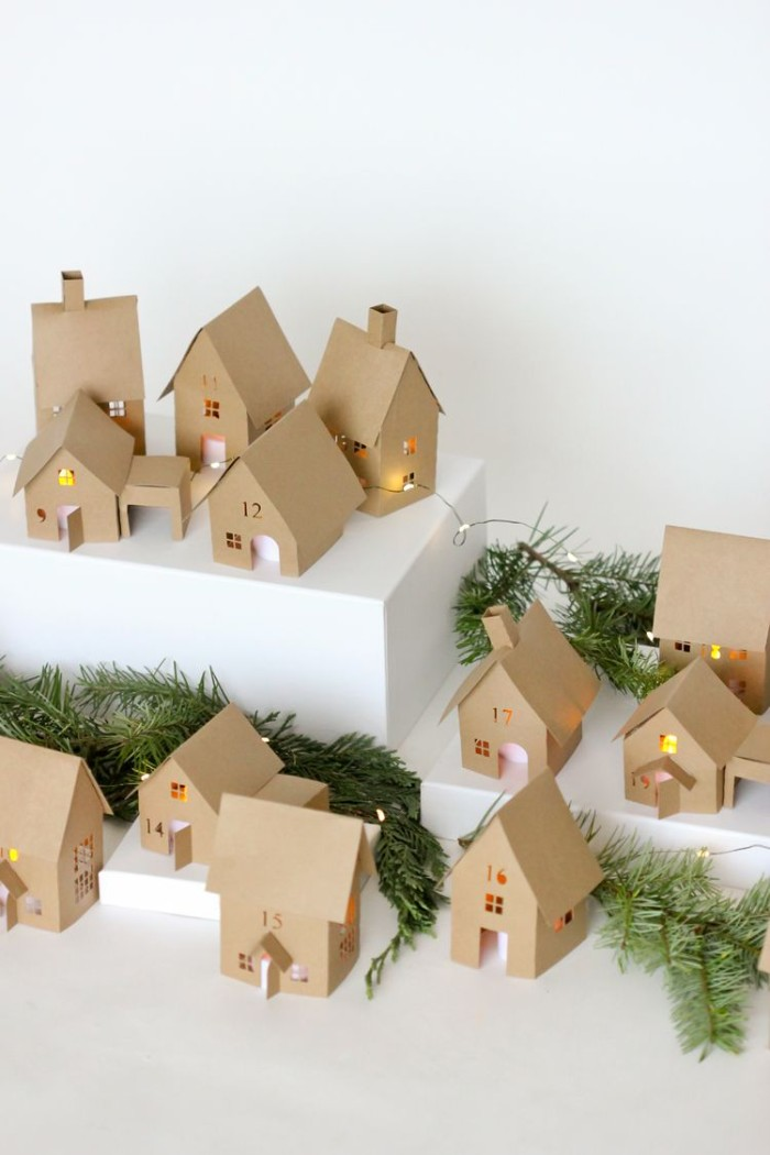 pine branches and lit string lights, placed on a white survace, among thirtheen decorations, shaped little houses, made from beige card, adult advent calendar suggestion