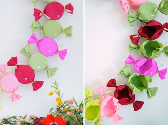 candy-shaped presents, made with tissue paper in different colors, forming a wreath, decorated with small, white number stickers, christmas advent calendar