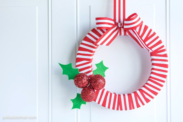 striped red and white wreath, decorated with three baubles, covered in red glitter, three holly leaves, made of green felt, and a large striped bow, christmas wreath