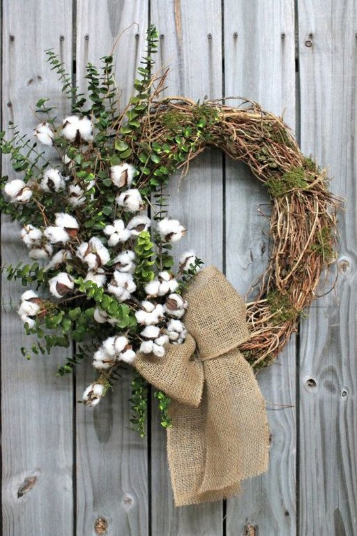 cotton seed pods on branches, with small green leaves, decorating a rustic wreath, made from thin, dried twisted branches, tied with a burlap bow