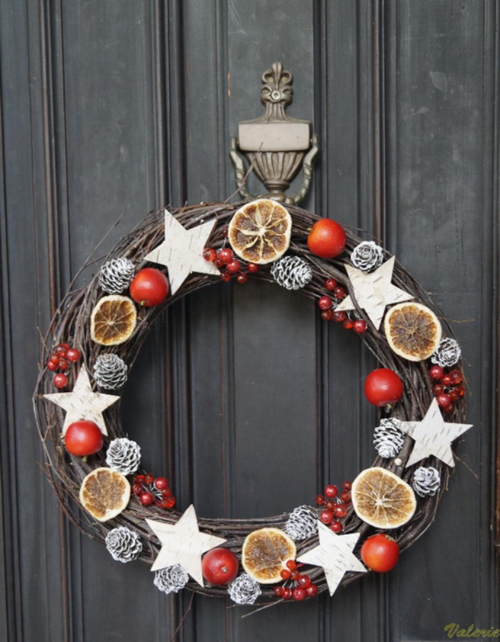 birch bark star shapes, decorating a diy christmas wreath, made from thin dried branches, and adorned with small pinecones, covered in silver paint, dried orange slices, and faux red berries in different sizes