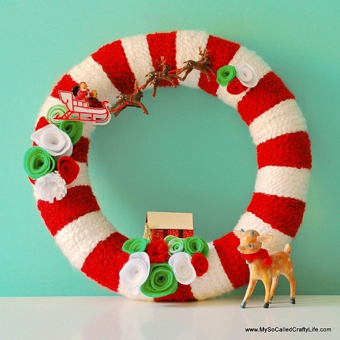 red and white, striped christmas wreath, decorated with small figurines, santa's reindeer sleigh, a little house, felt flowers in white, red and light green, holiday wreaths, a small deer toy, with a red scarf