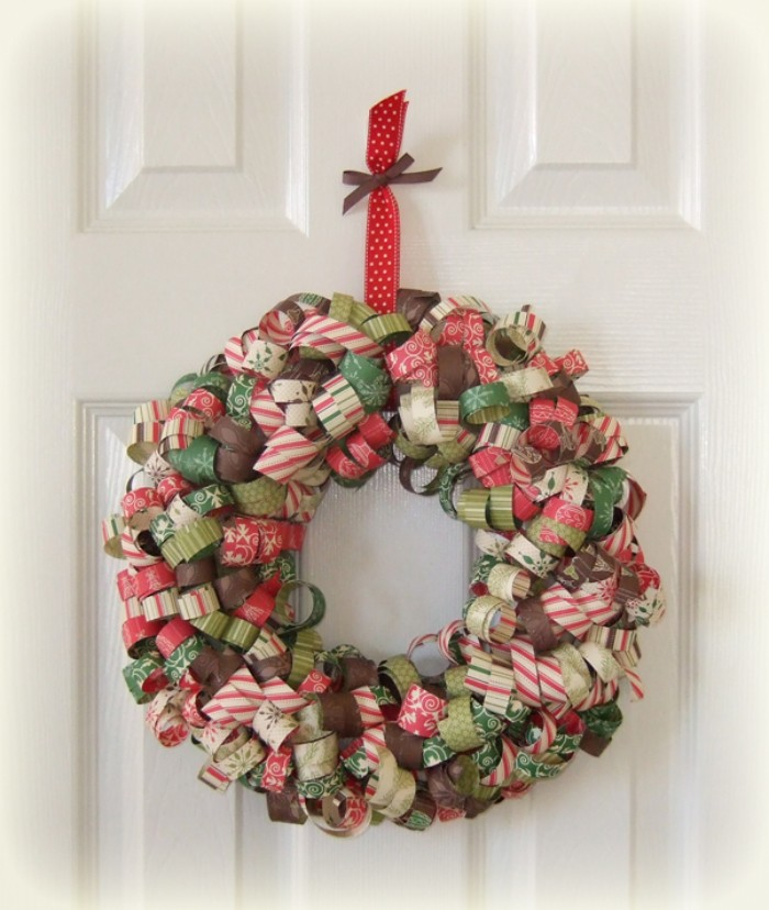 curled paper strips, in many different colors and patterns, stuck on a round frame, to form a christmas wreath, hanging on a white door, holiday wreaths