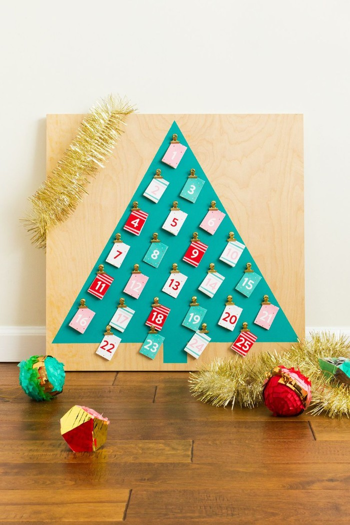 simple christmas tree shape, made of teal paper, stuck to a pale wooden board, decorated with 25 small numbered cards, in white and red, teal and pale pink, christmas countdown calendar, made simple
