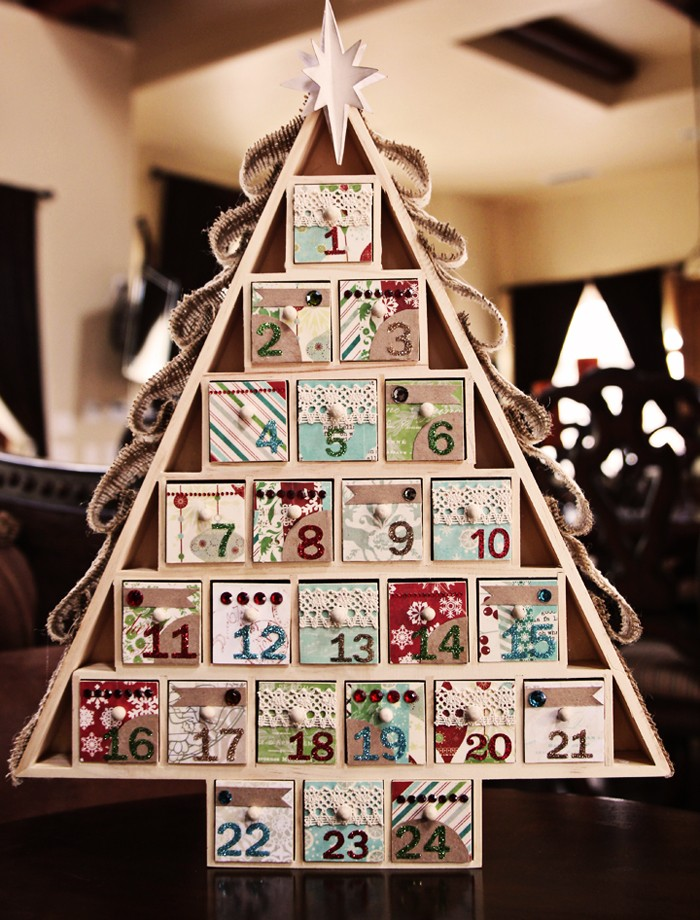 wooden christmas advent calendar, shaped like a triangular christmas tree, with 24 numbered compartments, each decorated with colorful patterned paper