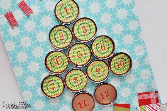 numbered mason jar lids, decorated with patterned, light green and red paper, organized in the shape of a christmas tree, fun advent calendars, on a light blue and white surface, with a floral pattern