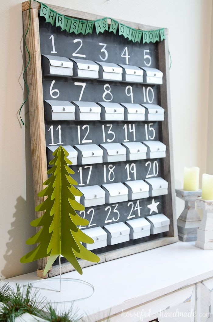 blackboard in a wooden frame, with 25 small grey boxes, there is a number, from 1 to 24, written in white chalk, above each one, fun advent calendars, there is a white star, above the 25th one