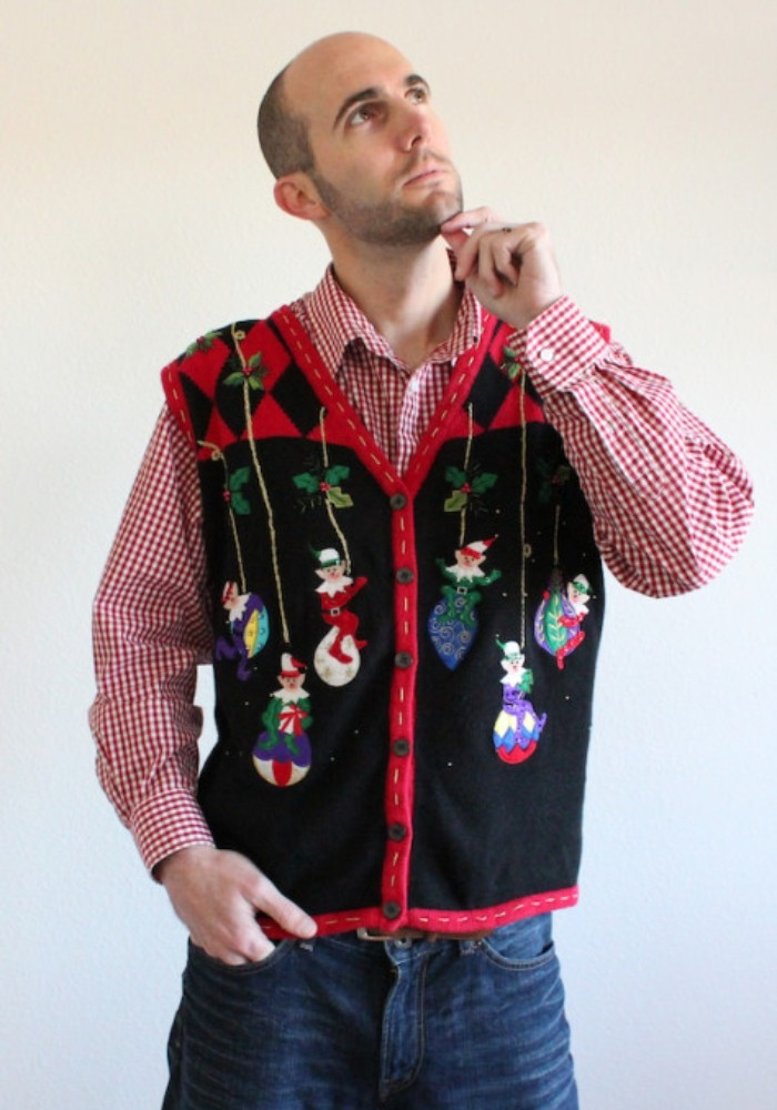 toughtful man in a checkered, red and white shirt, and blue jeans, wearing a black and red vest, decorated with elves, and baubles in different colors